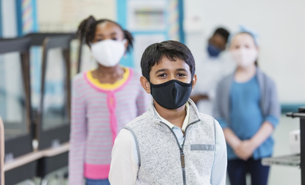 group of elementary school students in the classroom during the covid-19 pandemic, wearing face masks and standing six feet apart, social distancing.