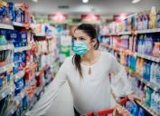 Woman wearing protective mask preparing for virus pandemic spread quarantine.Finding the right products on the shelves in the supermarket.Hygiene, cleaning and disinfection products.Budget buying.