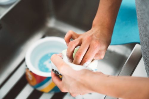 Unrecognizable woman hands washing dog bowl in the kitchen sink.