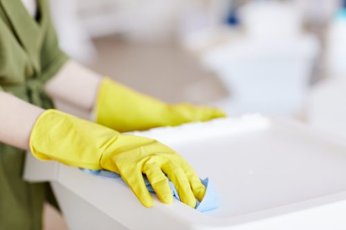 Close up of unrecognizable woman wearing yellow rubber gloves while cleaning plastic containers at home, copy space