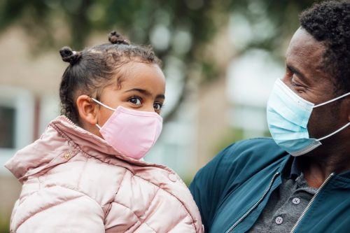 Close up of a young girl and her father wearing protective face masks during the Covid 19 pandemic outside.