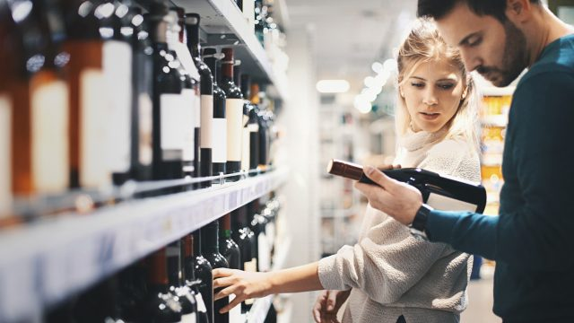 A young couple shopping for a bottle in a liquor store