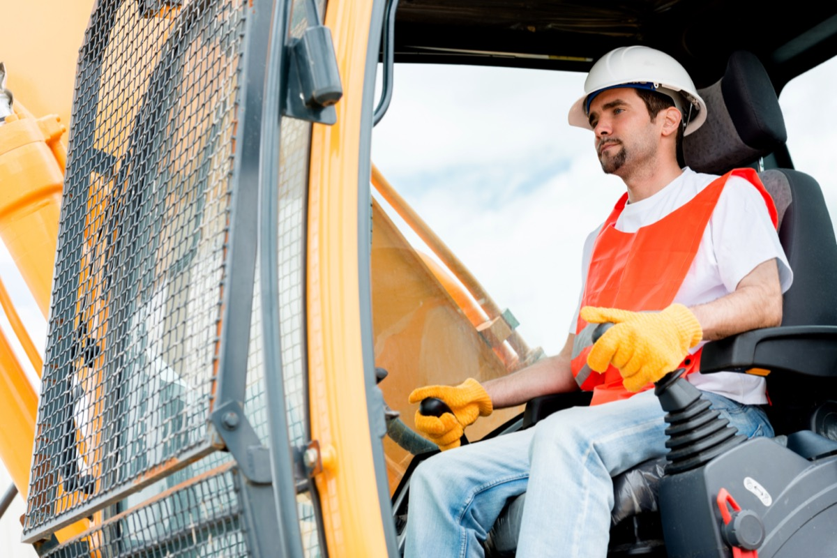 30-something man operating crane