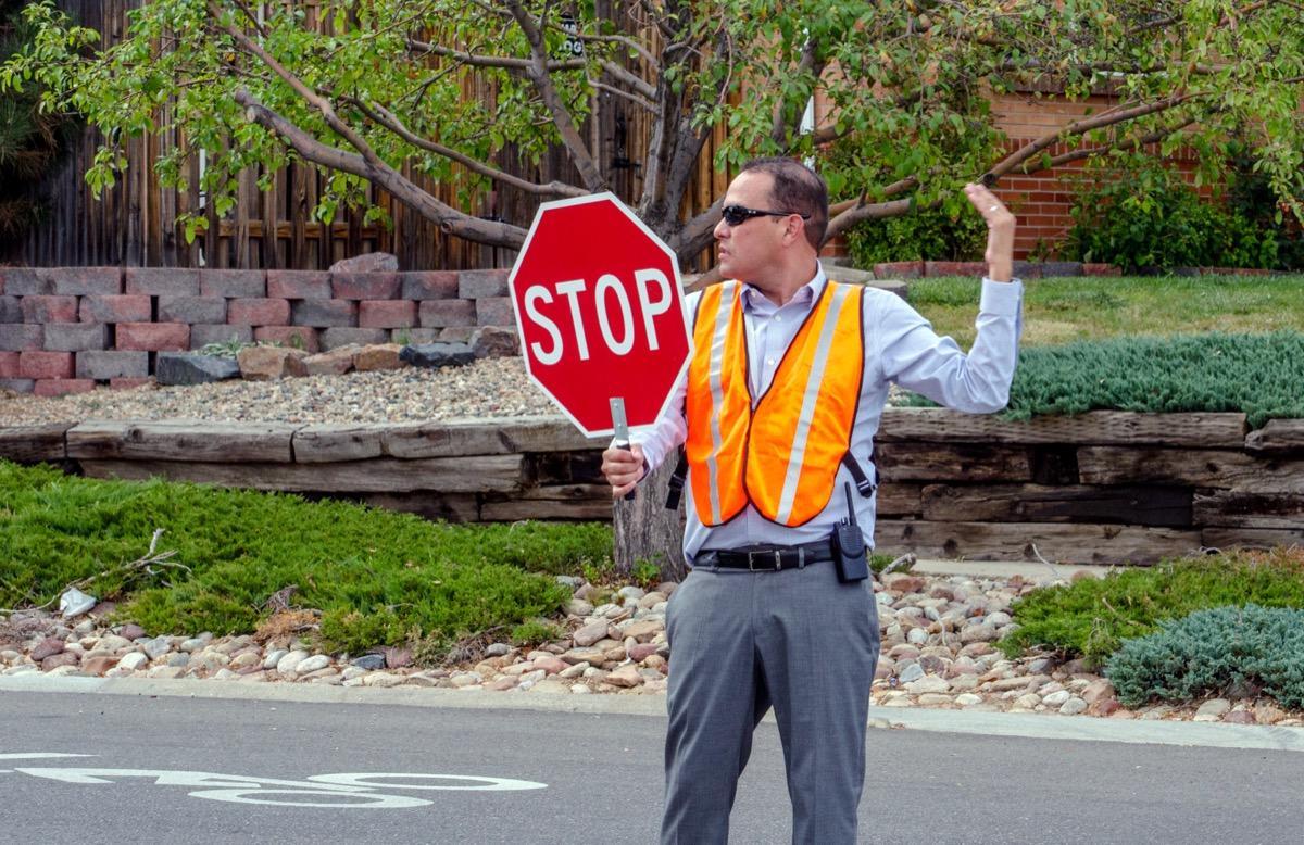 male crossing guard in orange vest gesturing to allow people across street