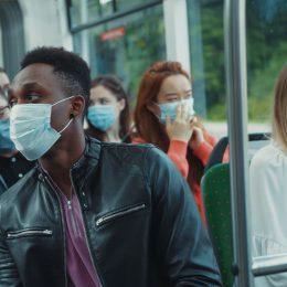 Blonde woman sneezes inside public tram. Scared people passengers immediately wearing face masks for virus prevention.