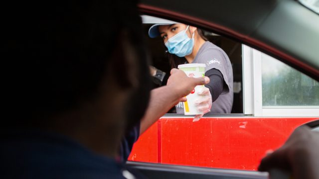 A man reaches for his food at the McDonalds drive-thru window as the employee wears a mask for protection.