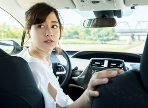 young woman driver turning back.