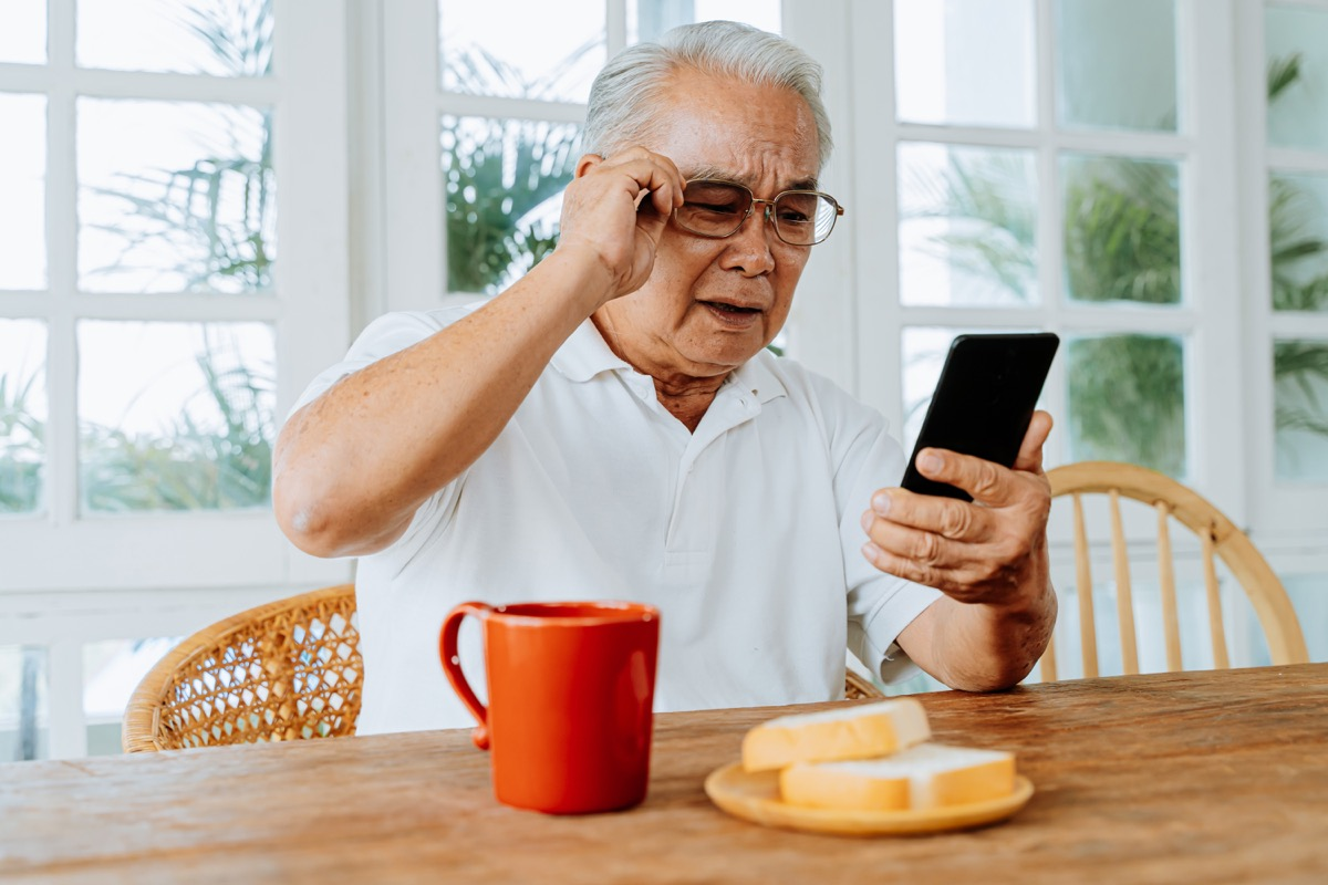 Senior man looking at phone