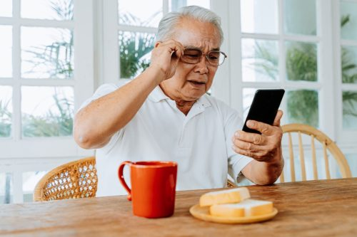 A male with eyesight problems wears glasses while squinting and reading messages on smartphone during breakfast at home.  An old man with blurred vision inside.