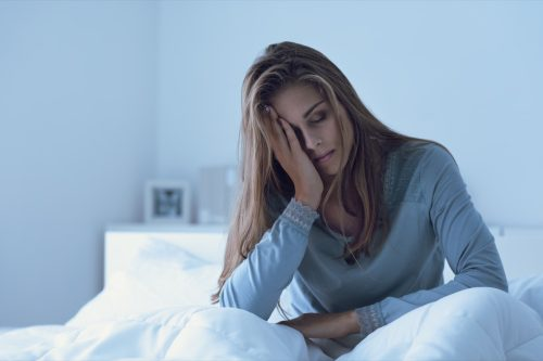 A depressed woman wakes up at night with her forehead touching and suffers from insomnia
