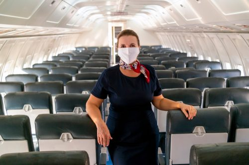 A flight attendant wearing a face mask onboard an empty plane