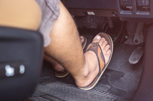 Man wearing flip-flop while driving
