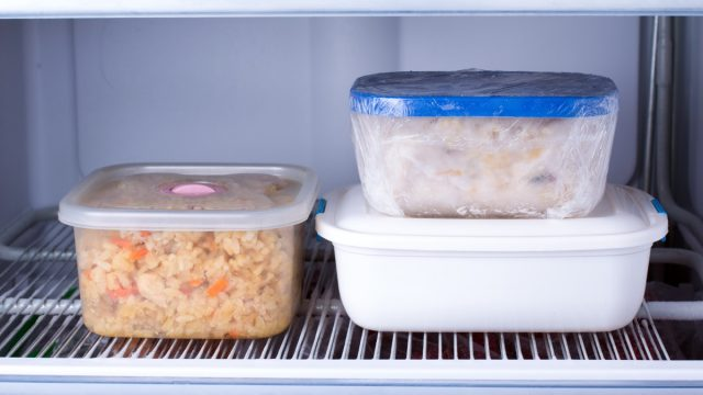 three food containers in a freezer