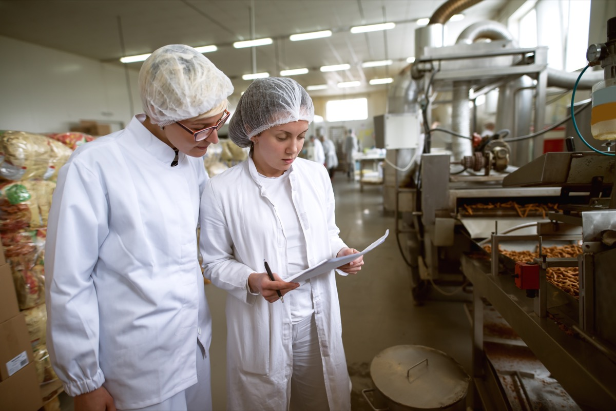 two food safety inspectors looking at papers on clip board