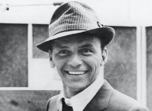 American singer and actor Frank Sinatra smiles at recording studio, 1950s.