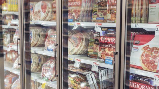 supermarket freezer case full of frozen pizzas