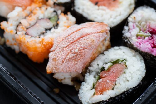 Overhead frozen japanese sushi food. Maki ands rolls with salmon, shrimp, crab and avocado.