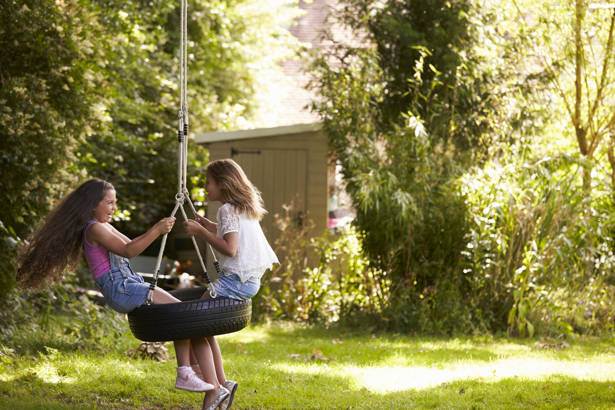 Two young girls playing on a tire swing