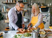 Senior men and women cutting fresh raw vegetable in kitchen