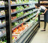 Portrait of a smiling worker taking a vegetables in supermarket