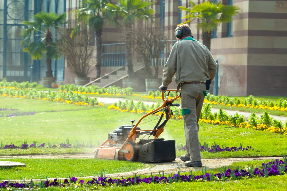grounds maintenance worker mowing lawn