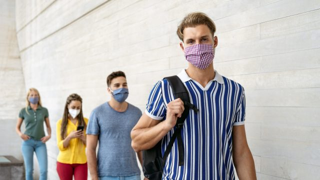 A group of young people wearing face masks while waiting in line