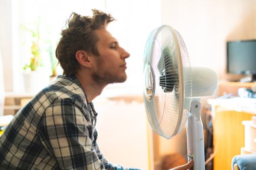 A person enjoying an electric fan, cooling his face at home during the summer heat