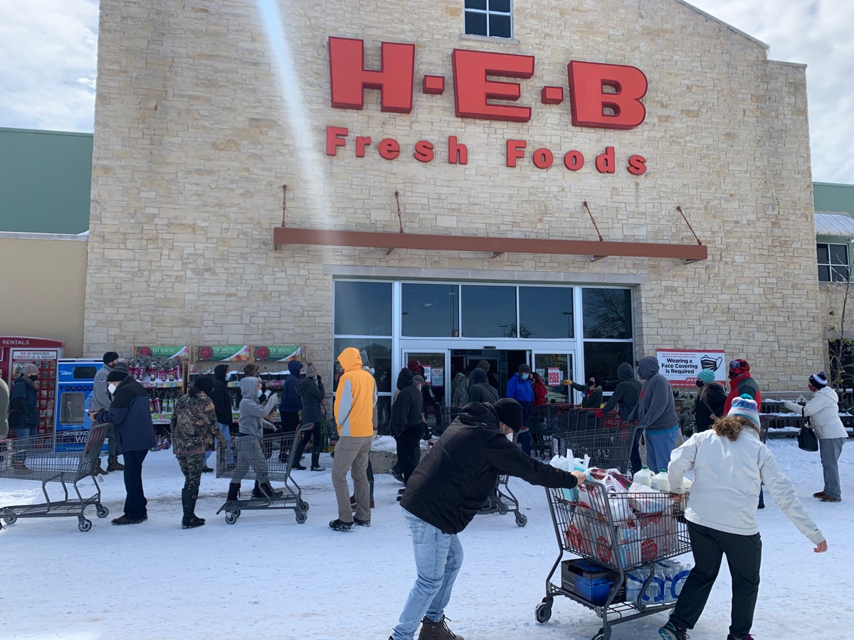 people standing around the exterior of an h-e-b supermarket