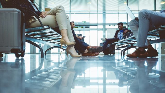Low angle shot of travelers sitting in airport lounge area, waiting to board plane at the departure gates