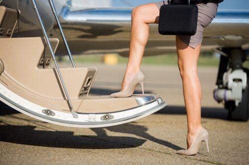 Legs of unknown businesswoman on the steps of private jet airplane.