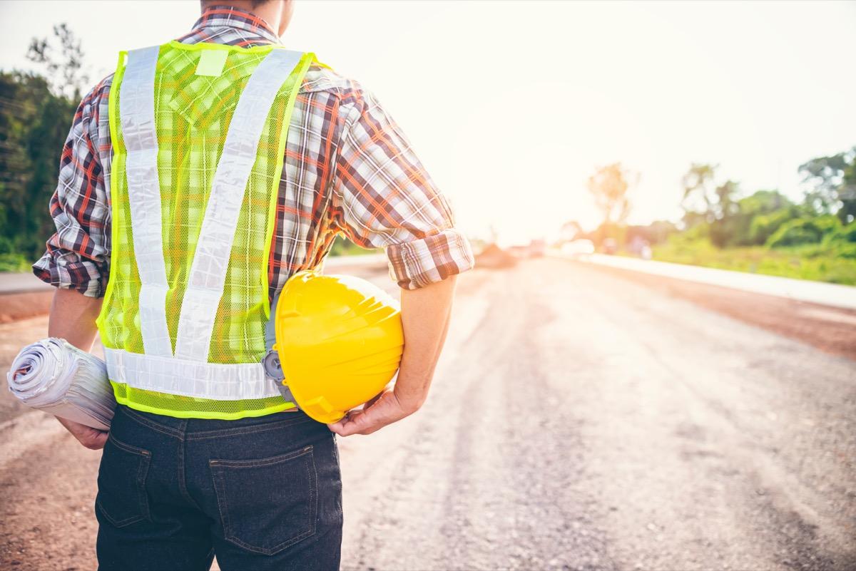 highway maintenance worker in yellow vest holding hard hat