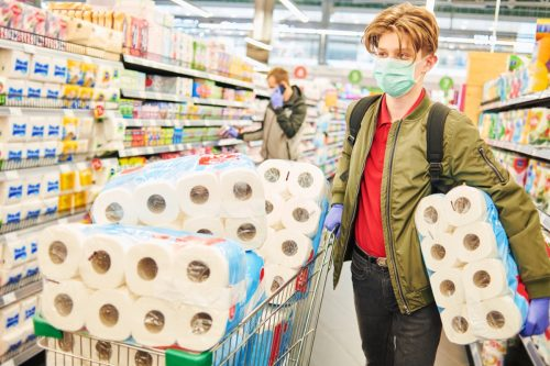 man in mask and protective gloves buying toilet paper in shop. Panic at coronavirus epidemic