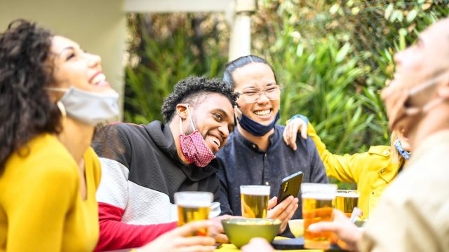 People smiling with beers and masks on chins celebrating Labor Day weekend