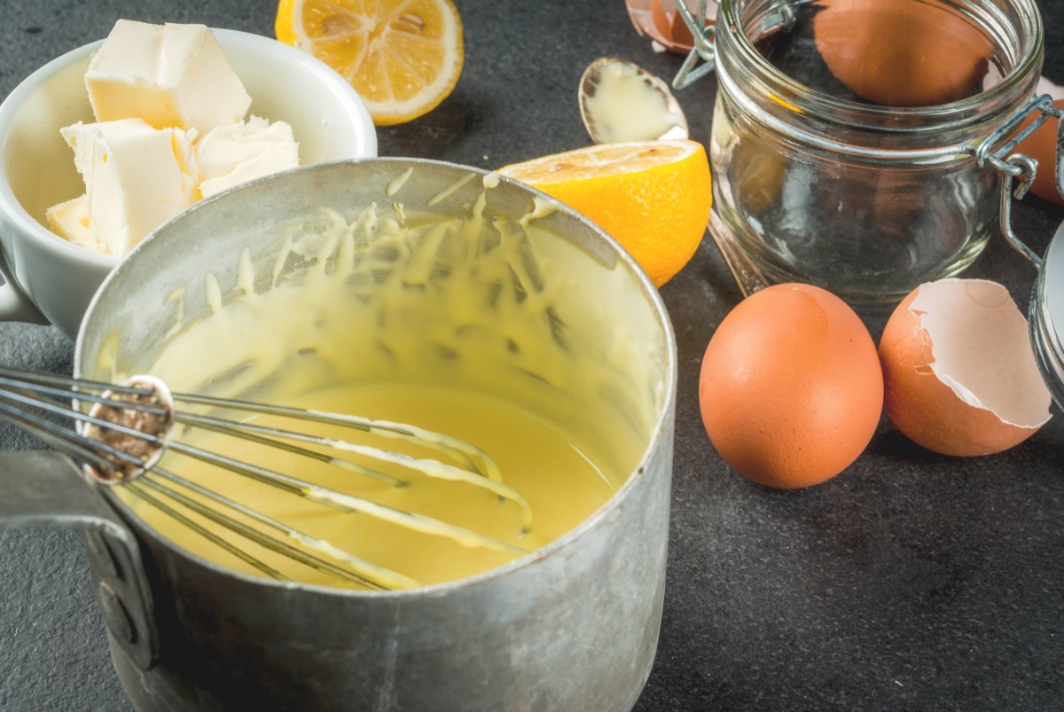 whisk in a metal bowl of hollandaise on a counter with eggs and butter and lemons