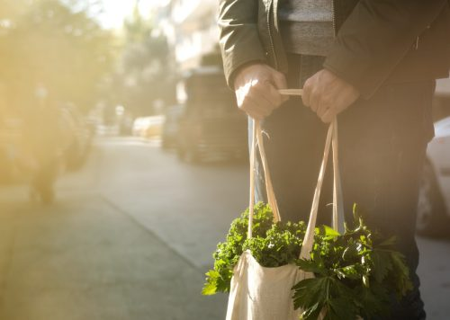 Young man holding reusable textile grocery bag with green vegetables