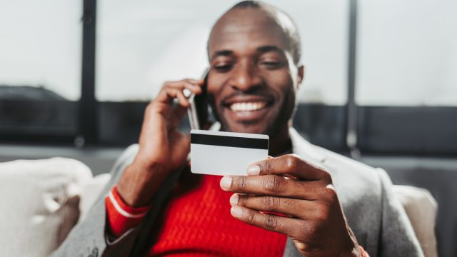 man taking a cell phone call and looking at credit card
