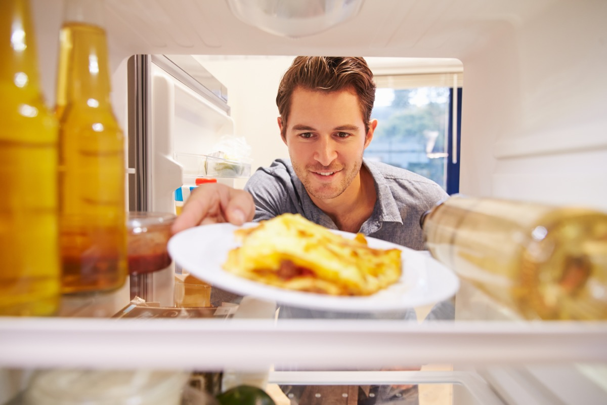man putting plate of eggs into the fridge