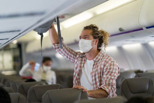Passenger putting his carry-on luggage in the overhead compartment and wearing a facemask inside the airplane during the COVID-19 pandemic