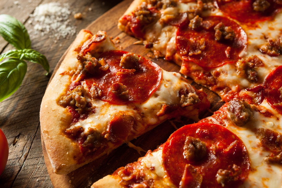 meat pizza with a slice cut out on wooden background