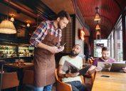 two young men ordering food from a server wearing a flannel shirt