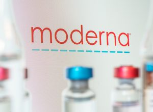 The Moderna company logo with vaccine vials in the foreground