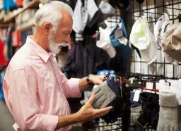 Senior person in sports and outdoor equipment store choosing to buy some gloves.