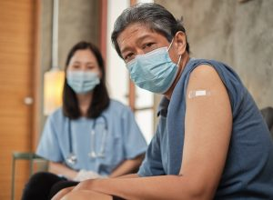 An elderly male patient has a plaster bandage on his arm after vaccinating against COVID-19.