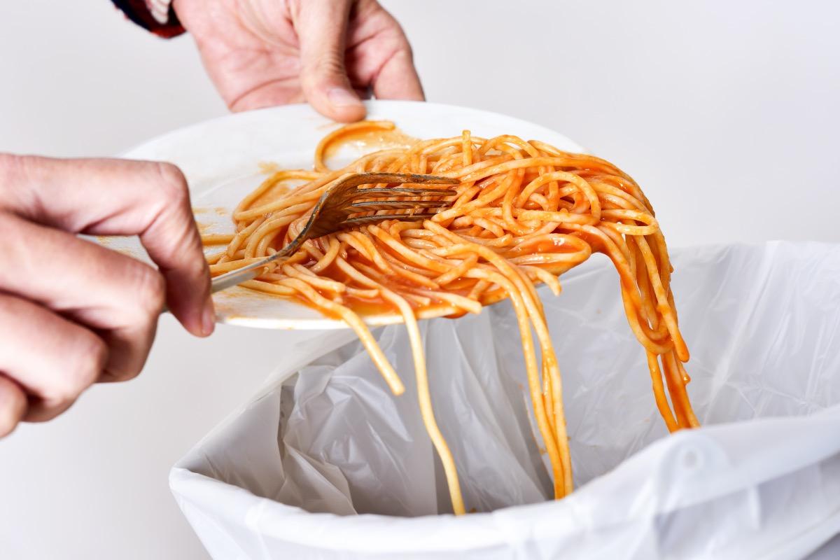person scraping spaghetti off white plate into trash