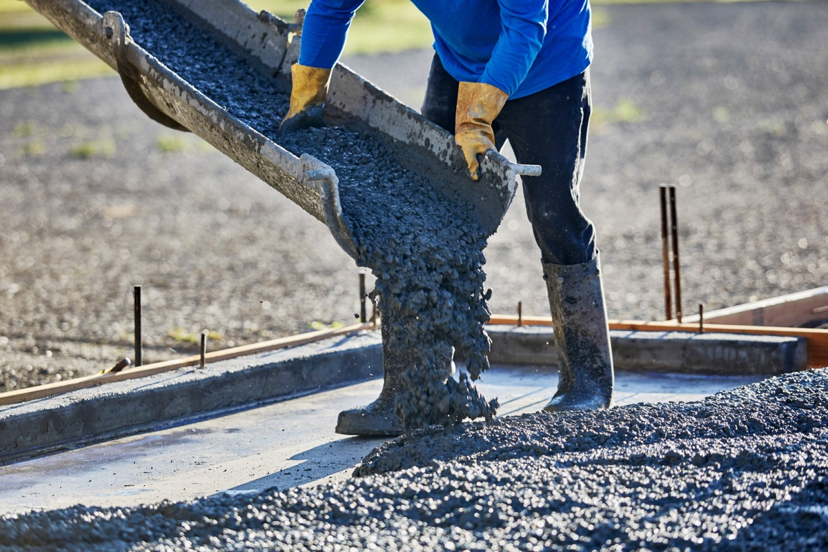 person pouring cement from chute outdoors