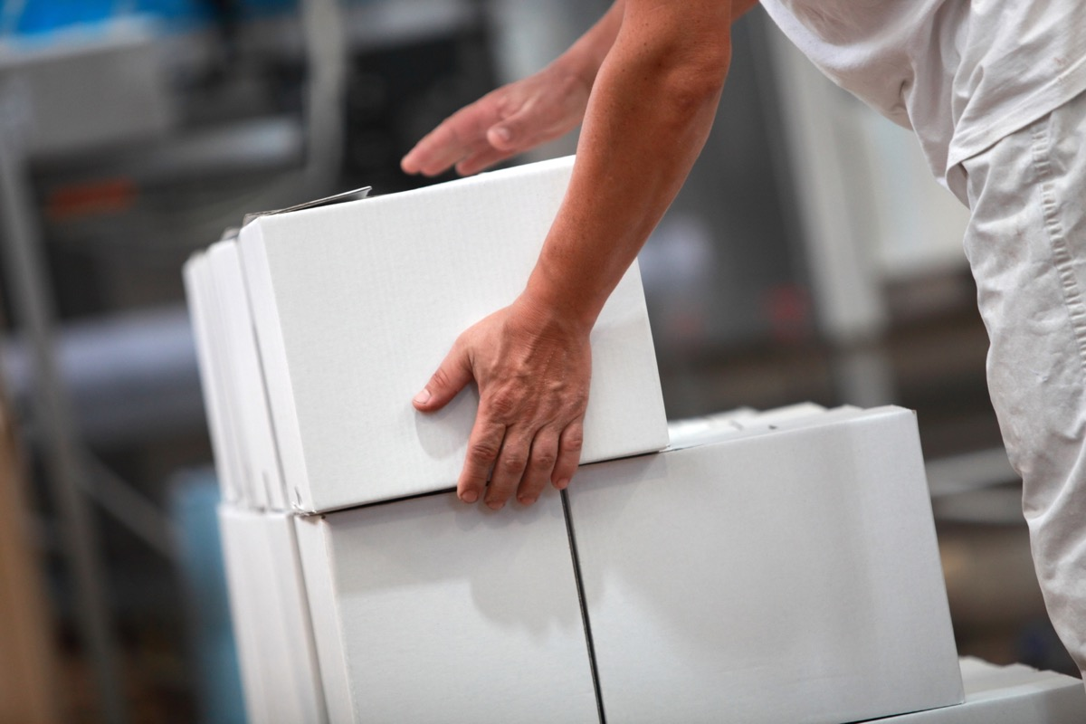 person holding a white cardboard box atop other cardboard boxes in a factory
