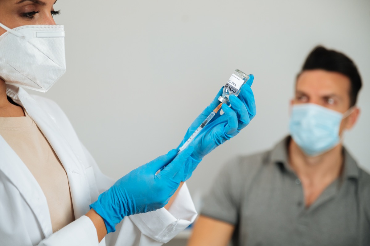 Crop anonymous doctor in gloves filling syringe with COVID 19 vaccine against blurred adult patient in hospital