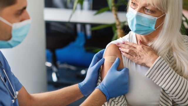 Covid-19 Vaccination. General Practitioner Vaccinating Older Female Patient Against Coronavirus With Antiviral Vaccine, Sticking Medical Adhesive Bandage On Arm After Injection In Centre Clinic
