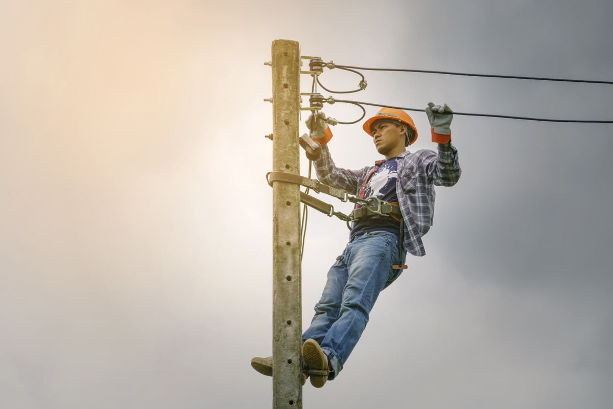 young worker holding on to power line