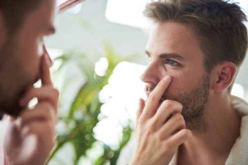 young man standing in front of mirror. He is looking precisely at face and touching skin under eyes with finger